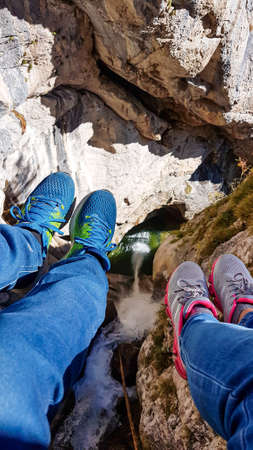 Two pairs of legs hanging from a ladder. There is a high mountain gorge below. Adventure park in Austrian Alps. There is a waterfall flowing in the gorde. Natural phenomenon 스톡 콘텐츠