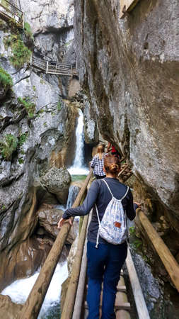 A woman in black blouse walking along a wooden, ladder pathway along a high gorge in Austrian Alps. There is a waterfall in front of her. Adventure park. Blue sky above. 스톡 콘텐츠