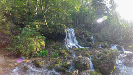 A panoramic view on a lush area of a small waterfall in Austrian Alps. There is a small pond below the waterfall.  The lush forest is flourishing. Calmness and serenity.