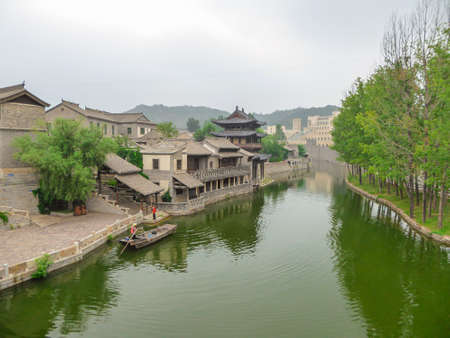 A view on the river in a small village in northern China. The river is overgrown with green plankton. Houses on both sides of the river. Serenity and calmness. Overcast due to the air pollution 免版税图像