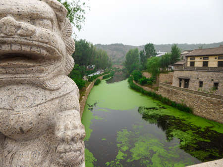 A view on the river in a small village in nothern China. The river is overgrown with green plankton. there is a lion figure on the bridge. Houses on both sides of the river. Serenity and calmness 免版税图像