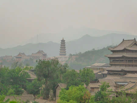 A panoramic view on a small village in northern China. A tall pagoda striking above the village.  There is a dense forest around. Rural areas. Tradition meets modernisation. Overcast and air pollution