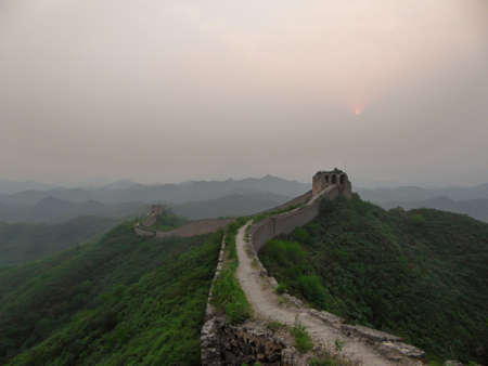 A panoramic view on an unrenewed Gubeikou part of Great Wall of China. The wall is spreading on tops of mountains. Many watchtowers on the peaks. Dense forest around it. World wonder. Tradition