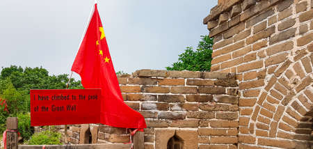 Chinese flag and board saying 'you have climbed to the top of Great Wall' placed on the top of Jinshanling part of Great Wall of China. Dense forest around it. World wonder. Tradition and achievement