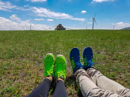 Two pairs of legs with whoes on lying on a vast pasture in Xilinhot in Inner Mongolia. In the back there is a heap of stones (aobao) and a lot of wind turbines. Endless grassland. Blue sky with clouds