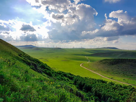 A panoramic view on a hilly landscape of Xilinhot in Inner Mongolia. Endless grassland with a few wind turbines between. Blue sky with thick, white clouds. A small gravel road through the pasture. 免版税图像