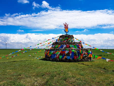 Heap of stones (Aobao) build on a vast pasture in Xilinhot in Inner Mongolia. The heap has a lot of colorful prayer flags attached to it. Endless grassland. Blue sky with white clouds. Religious place