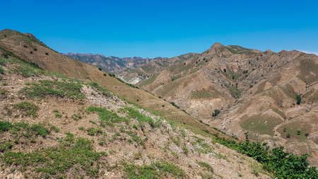 A panoramic view on Daqing mountains in Inner Mongolia. Endless mountain chains. The slopes are mostly barren, overgrown with small bushes and grass. Desolated landscape. Bio diversity of a region 免版税图像
