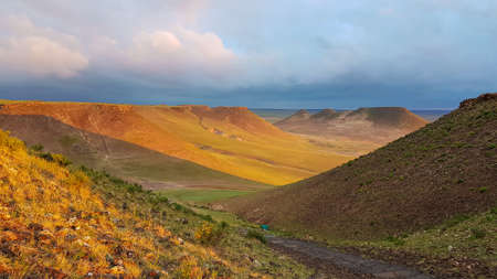 A colofrul sunrise seen from a small hill in the suburbs of Xilinhot, Inner Mongolia. The rising sun paints the hills orange. Endless chain of Pingding Mountain. The mountains have flat and wide peaks
