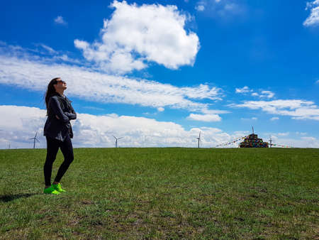 A woman standing on a vast pasture in Xilinhot in Inner Mongolia. In the back there is a heap of stones (aobao) with colorful prayer flags attached to it. Endless grassland. Blue sky with white clouds