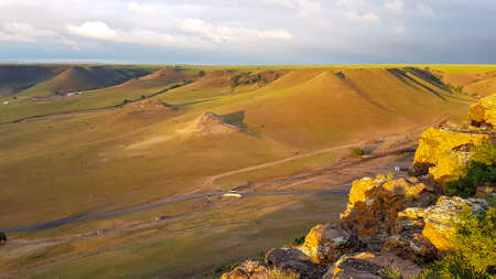 A colorful sunrise seen from a small hill in the suburbs of Xilinhot, Inner Mongolia. The rising sun paints the hills orange. Endless chain of Pingding Mountain. The mountains have flat and wide peaks