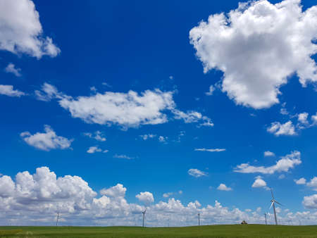 A field of wind turbines build on a vast pasture in Xilinhot in Inner Mongolia. Natural resources energy. Clean energy. Endless grassland. Blue sky with white, thick clouds. Serenity