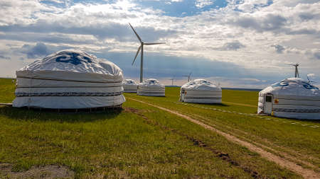 A few white, traditional yurts located on a pasture in Xilinhot in Inner Mongolia. Endless grassland. Blue sky with a few thick clouds. Wind turbines in the back. Clean energy. Nomadic way of life.