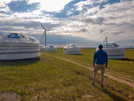 A man standing in front of white, traditional yurts located on a pasture in Xilinhot in Inner Mongolia. Endless grassland. Blue sky with thick clouds. Wind turbines. Clean energy. Nomadic way of life