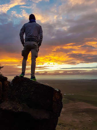 A man admiring a sunrise from a small hill in the suburbs of Xilinhot, Inner Mongolia. The sky is painted in orange, red and pink. Soft colors of sunrise. There is the city in the back. Daybreak