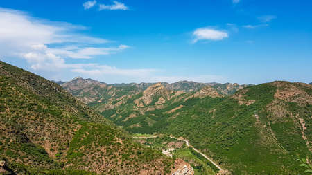 A panoramic view on Daqing mountains in Inner Mongolia. Endless mountain chains. The slopes are overgrown with small bushes and grass. Desolated landscape. Clear and sunny. Bio diversity of a region 免版税图像