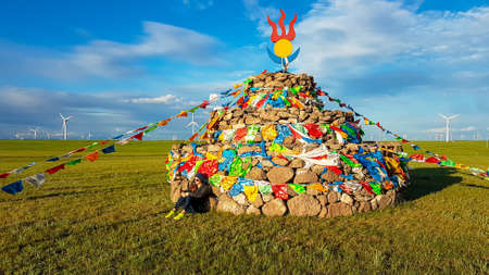 A woman in a beanie sitting on a vast pasture under a heap of stones (aobao) with colorful prayer flags attached to it. There are a lot of wind turbines in the back. Blue sky with white clouds. Spirit