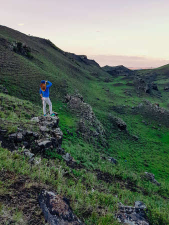 A man standing on a green hill in Xilinhot, Inner Mongolia and enjoys a sunset. He is wearing a cowboy hat. Endless grassland. The sun starts setting behind the horizon, coloring the sky orange 免版税图像