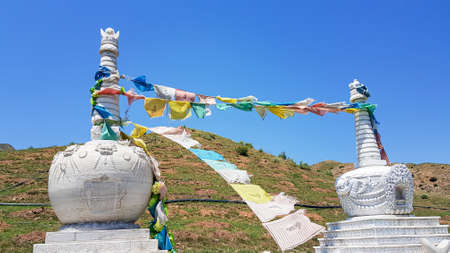 Two white heap of stones (aobao) with panoramic view on Daqing mountains in Inner Mongolia. They have a few colorful prayer flags attached. Endless mountain chains. Desolated landscape. Religion 免版税图像