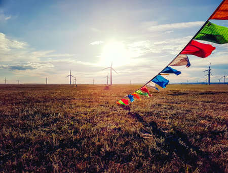 Colorful prayer flags attached to a heap of stones (aobao) on a vast grassland in Xilinhot, Inner Mongolia. The sun is setting behind the horizon. Golden hour. A field of wind turbines in the back
