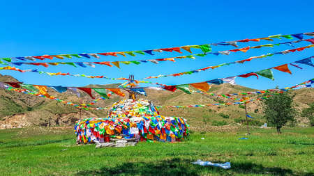 A big white heap of stones (aobao) with panoramic view on Daqing mountains in Inner Mongolia. It has a few colorful prayer flags attached to it and waving around it. Desolated landscape. Spirituality