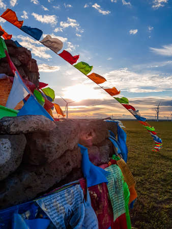 Heap of stones (Aobao) build on a vast pasture in Xilinhot in Inner Mongolia. The heap has colorful prayer flags attached to it. The sun is setting behind the horizon. Golden hour. Wind turbines