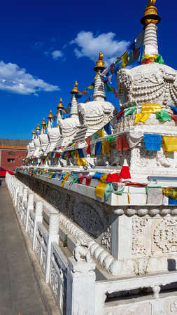 A row of white stupas wrapped with colorful prayer flags in Hohhot, Inner Mongolia. The stupas are richly decorated with golden elements. Spirituality and religion. 免版税图像