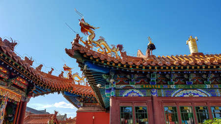 A close up on the richly decorated rooftop of a Chinese-style temple in Hohhot, Inner Mongolia. There is a golden dragon at the edge of the rooftop, guarding the temple from bad spirits. Tradition
