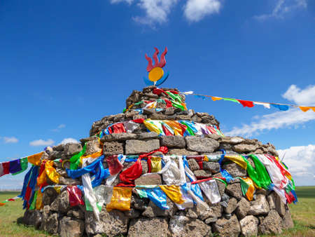 Heaps of stones (Aobao) build on a vast pasture in Xilinhot in Inner Mongolia. The Heaps has a lot of colorful prayer flags attached to it. Endless grassland. Blue sky with white clouds. Religious place 免版税图像