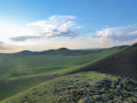 A panoramic view on a hilly landscape of Xilinhot in Inner Mongolia. Endless grassland with a few wildflowers between. The sun starts to set, coloring the sky orange. Blue sky with thick, white clouds