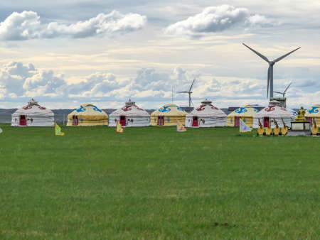 Yellow and white traditional yurts located on a pasture in Xilinhot in Inner Mongolia. Endless grassland. Blue sky with a few thick clouds. Wind turbines in the back. Clean energy. Nomadic way of life