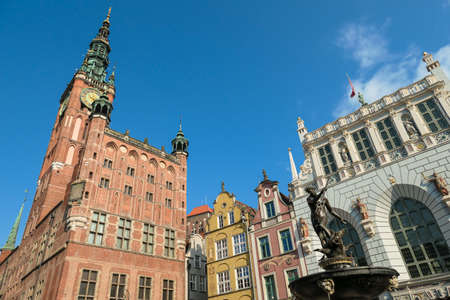 The Neptune's Fountain in Old Town of Gdansk, Poland. The fountain is located in the central point. Town Hall building in the back. City tour. Clear and bright day.