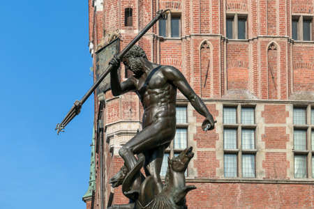 A close up view on the Neptune's Fountain in Old Town of Gdansk, Poland. The fountain is located in the central point. Red bricked Town Hall building in the back. City tour. A bit of overcast