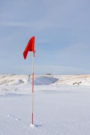golf drapeau: Drapeau rouge de Golf dans la neige Banque d'images