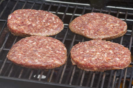 broiling: Raw  Burgers on a Barbecue Grill close-up