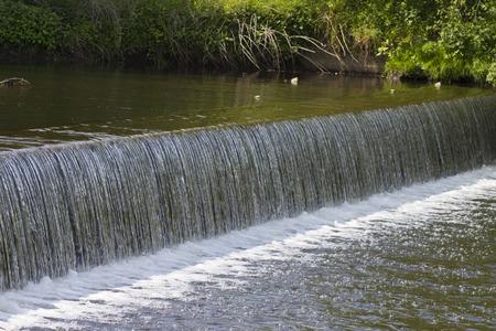 weir water cascades down stream