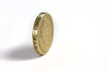 uk money: One pound coin on its edge on a white background