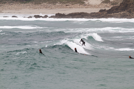 sennen: SENNEN COVE, CORNWALL, ENGLAND - 22 OCTOBER 2014: Surfers catching a wave on a cold autumn day,  on 22 October 2014 in Sennen Cove cornwall England.