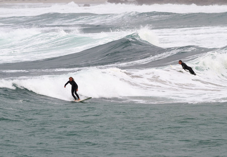 surfers: SENNEN COVE, CORNWALL, ENGLAND - 22 OCTOBER 2014: Surfers catching a wave on a cold autumn day,  on 22 October 2014 in Sennen Cove cornwall England.