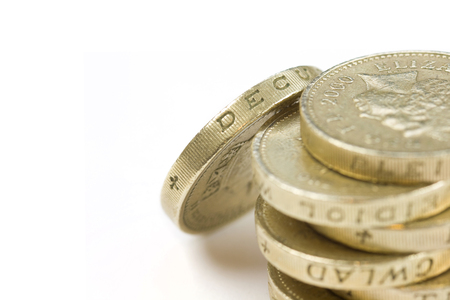 gold and silver coins: Stack of One pound coins on a white background