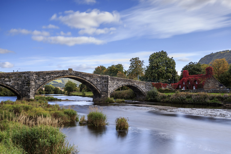 court room: Pont Fawr, famous medieval stone bridge across the river Conwy, and court house covered in red ivy  Llanrwst, Caernarfon, North Wales
