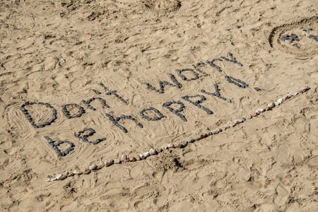 dont worry: Dont Worry Be Happy, with stones in sand.