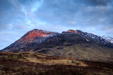 glencoe: with the sun setting behind me, the peaks of this mountain, light up red.  Glencoe, Scotland UK.