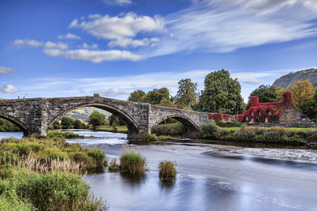 Pont Fawr, famous medieval stone bridge across the river Conwy, and court house covered in red ivy  Llanrwst, Caernarfon, North Wales