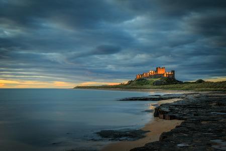 De zonsopgang van het Bamburghkasteel op de kustlijn van Northumberland