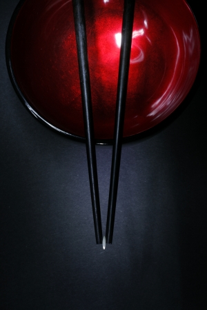 lacquerware: Pair of chopsticks with a single grain of rice, resting on a lacquerware bowl