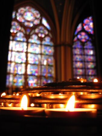 prayer candles: Prayer candles in Notre Dame Cathedral, Paris with out-of-focus stained glass in the background