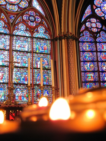 prayer candles: Stained glass of the Notre Dame cathedral, Paris with blurred prayer candles in the foreground, providing copy space