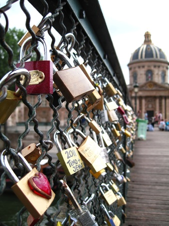 affix: Paris, France - June 14 2011  Love padlocks fixed on the Pont des Arts bridge as a symbol of love and commitment  Love padlocks are an international phenomenon, including countries as diverse as Italy and Uruguay  Editorial