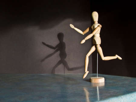 artists dummies: Artists mannequin running creating a shadow Stock Photo